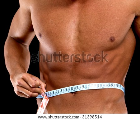 man with a muscular body measuring his abs - lose weight series - stock photo
