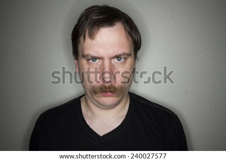 man with a mustach giving an intense stare down - stock photo