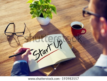 Man with a Notepad with Text Startup - stock photo