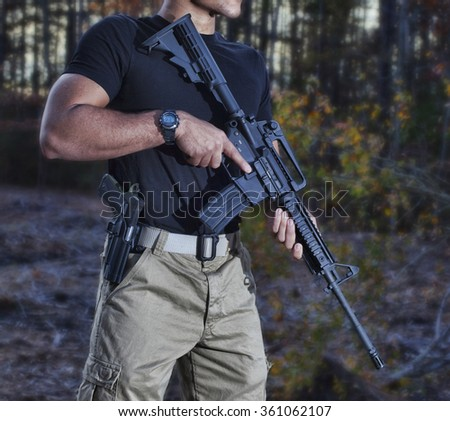 Man with a pistol and an AR-15 in the woods - stock photo