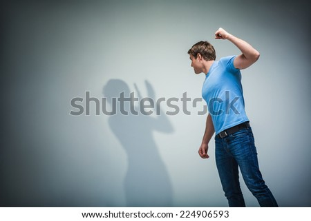 Man with a shadow in studio - stock photo