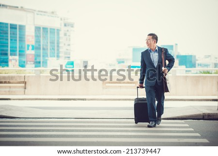 Man with a suitcase crossing the road to leave the airport - stock photo