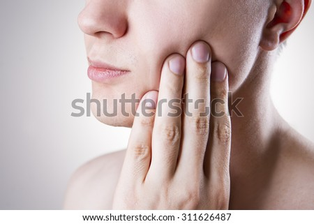 Man with a toothache. Pain in the human body on a gray background - stock photo