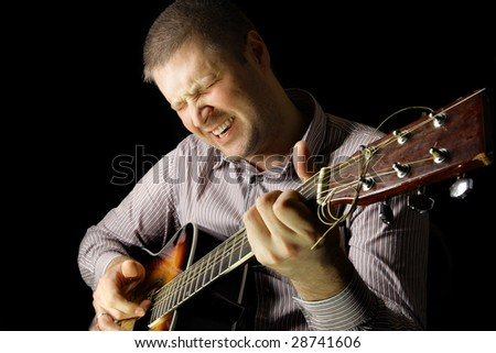 Man with acoustic guitar over black background - stock photo