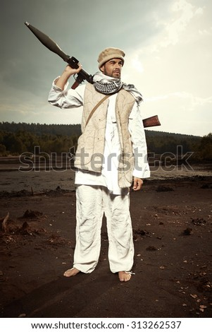 Man with AK-47 Kalashnikov handgun and RPG bazooka in traditional dress - stock photo
