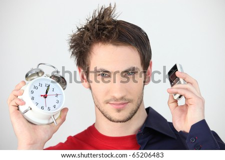 Man with an alarm clock and a mobile phone in hand - stock photo