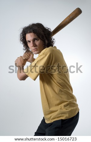 Man with an angry expression holds a baseball bat. Vertically framed photograph - stock photo