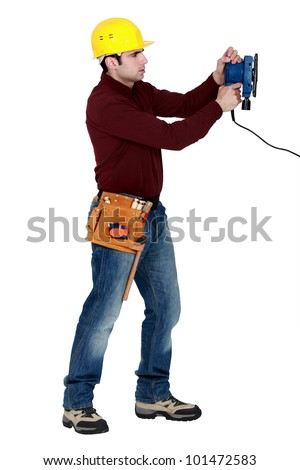 Man with an electric sander - stock photo