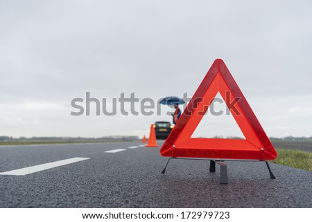 man with an umbrella besides his broken car alongside a road in the middle of nowhere - stock photo