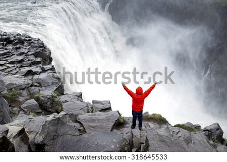 Man with arms spread standing in front of Dettifoss - the most powerful waterfall in Europe  - stock photo