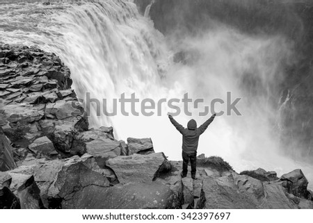 Man with arms spread standing in front of Dettifoss - the most powerful waterfall in Europe in black and white - stock photo