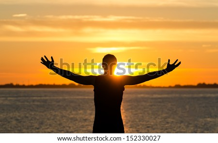 Man with arms wide open on the beach at sunrise - stock photo