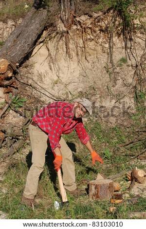 Man with axe chop logs for firewood.Ukraine - stock photo