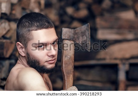 Man with axe in hands near firewood stock - stock photo