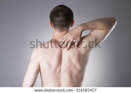 Man with backache. Pain in the human body on a gray background - stock photo