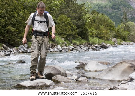 Man with backpack crossing a river in the mountains - stock photo