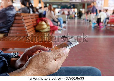 Man with backpack holding cell phone at bus terminal. - stock photo