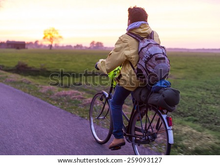 Man with backpack traveling by bicycle. - stock photo