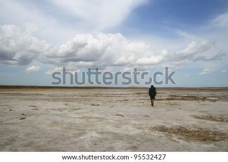 Man with backpack walking among waste landscape, salty lake Baskunckhak in summer - stock photo