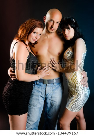 Man with bare chest and two beautiful girls adoring him - stock photo