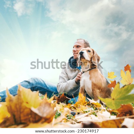 Man with beagle on autumn view landscape - stock photo