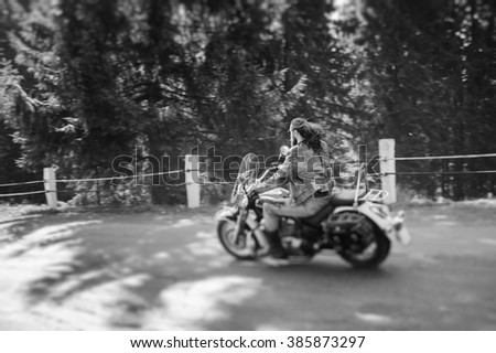 Man with beard driving his cruiser motorcycle by nice road in the forest. Man is wearing leather jacket and jeans. Back view. Tilt shift lens blur effect. Black and white - stock photo