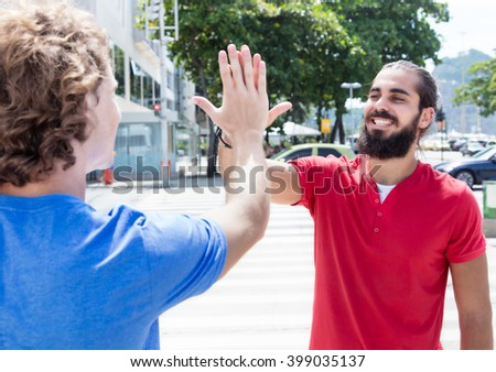 Man with beard give high five to caucasian guy - stock photo