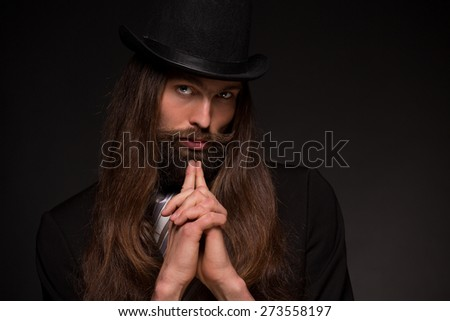 Man with beard in black topper and black suit think crossing his hands on dark background - stock photo