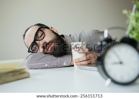 Man with beard in glasses sleeps in office on the table over laptop with coffee in hand - stock photo
