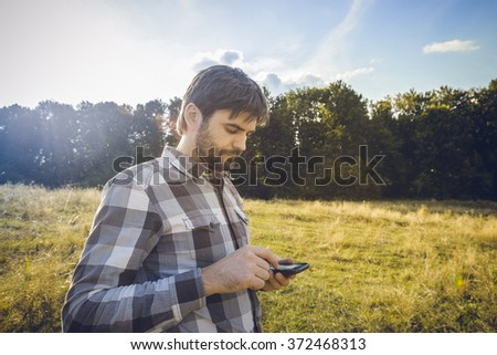 Man with beard looking at his smartphone while sundown Bearded man texting sms on his phone Man using apps for travel or gps navigation help or reading news and texts using 3g and 4g - stock photo