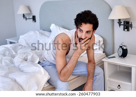 man with beard sitting on bed at home - stock photo
