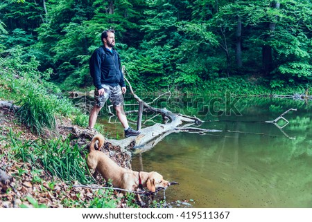 Man with beard standing on floating tree log by the lake shore and looking at the distance. Small yellow dog is playing near by. - stock photo