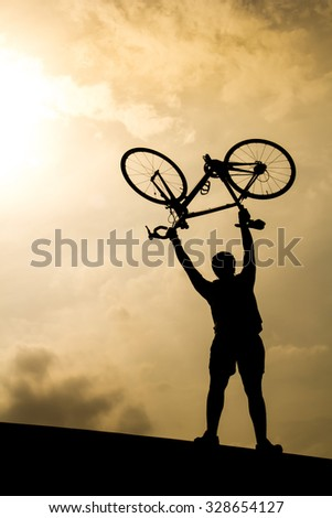 Man with bicycle lifted above him in the evening, Silhouette style. - stock photo