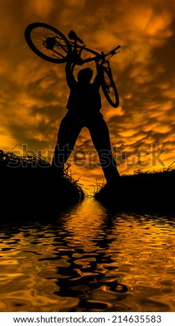 man with bicycle reflected on lake during sunset - stock photo