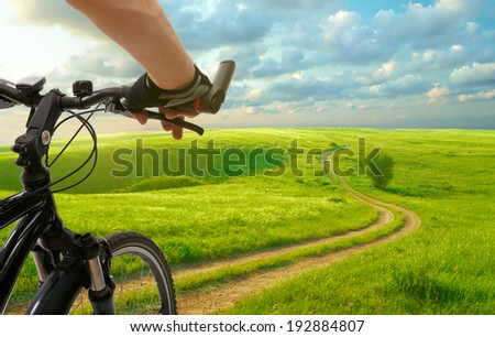 Man with bicycle riding country road - stock photo