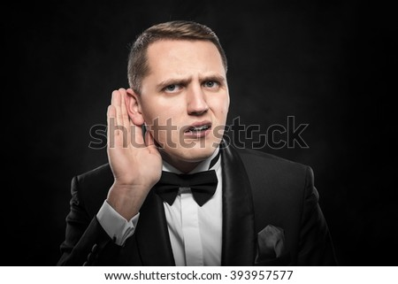 Man with big ear listening something on a dark background. - stock photo