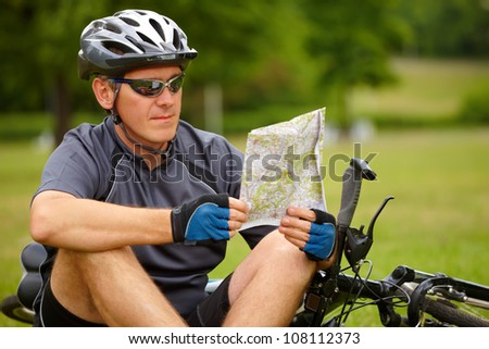 Man with bike checking map and looking around. - stock photo