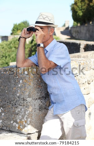 Man with binoculars and a hat - stock photo
