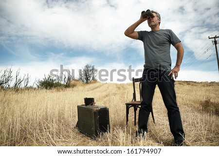 Man with binoculars standing in a field - stock photo