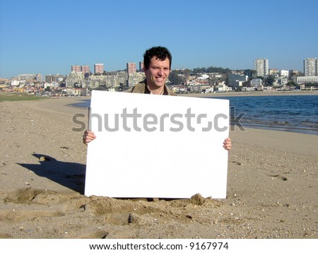 man with blank billboard in the beach - stock photo