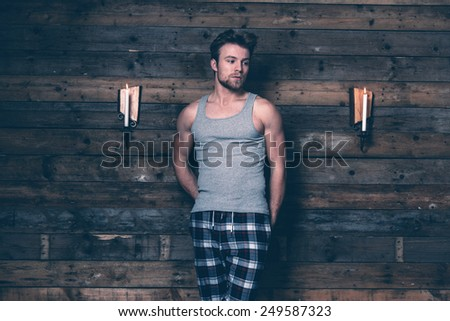 Man with blonde hair wearing gray singlet shirt and blue flannel pants. Standing against wooden wall inside wooden cabin. - stock photo