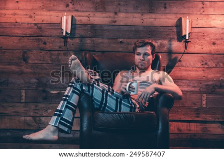 Man with blonde hair wearing winter sleepwear. Sitting in leather chair inside wooden cabin. - stock photo