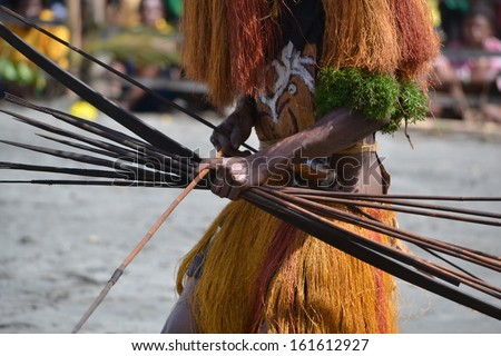 Man with bow and arrow traditional tribal weapon - stock photo