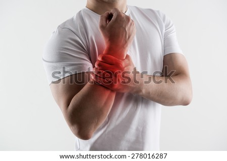Man with broken wrist. Young male massaging injured hand in pain. Concept of emergency and bone fracture treatment. - stock photo