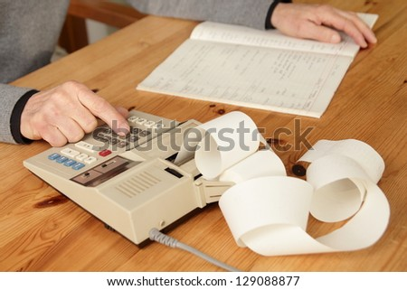 Man with calculator and book - stock photo