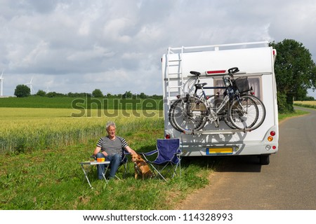 Man with camper in agriculture landscape - stock photo