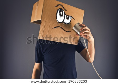 Man with cardboard box on his head using tin can telephone for conversation. Angry face expression. - stock photo