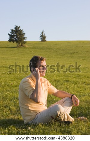 Man with cell phone talking while sitting in a meadow at sunset/sunrise - stock photo