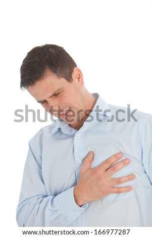 Man with chest pains grimacing in agony as he experiences the first signs of a heart attack or infarct - stock photo