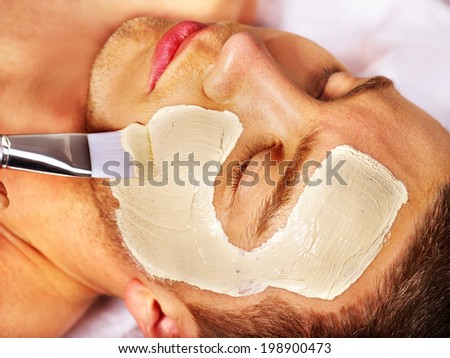 Man with clay facial mask in beauty spa. - stock photo